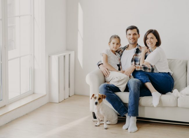 Family, togetherness and relationnship concept. Happy man embraces daughter and wife, sit on comfortable white sofa in empty room, their pet sits on floor, make family portrait for long memory